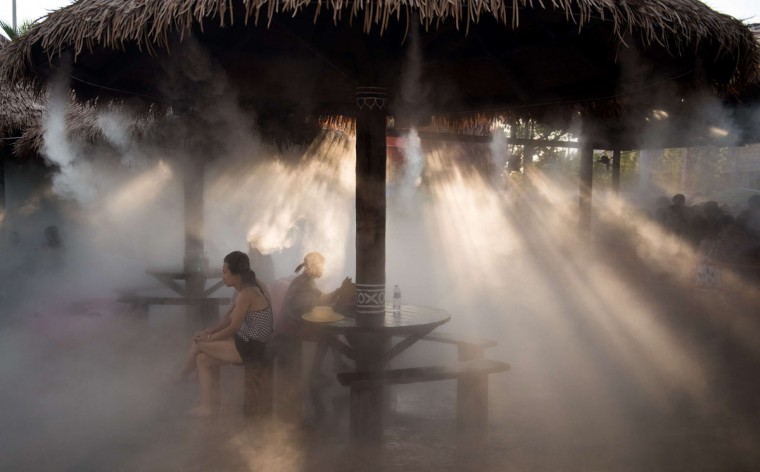 People cool down under a sprinkler in a water park in Shanghai on August 5, 2015. Typhoon Soudelor is set to bring an end to the heatwave affecting the region over the weekend, according to local reports. (AFP Photo/Johannes Eisele)