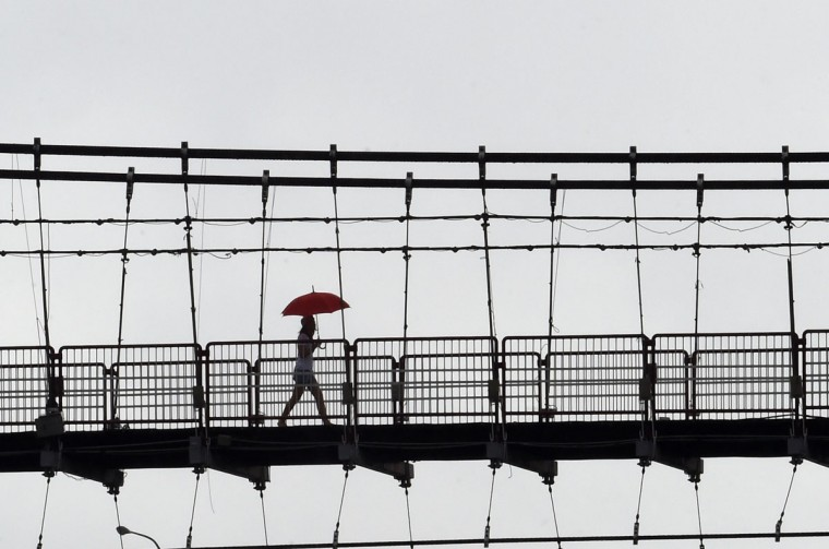 A local resident walks on a suspension bridge as typhoon Soudelor approaches in Pitan, the Xindien district in the New Taipei City on August 7, 2015. Taiwan's Central Weather Bureau predicted the storm would make landfall sometime. It has already forced the evacuation of more than 2,000 people from outlying islands popular with tourists. (AFP Photo/Sam Yeh)