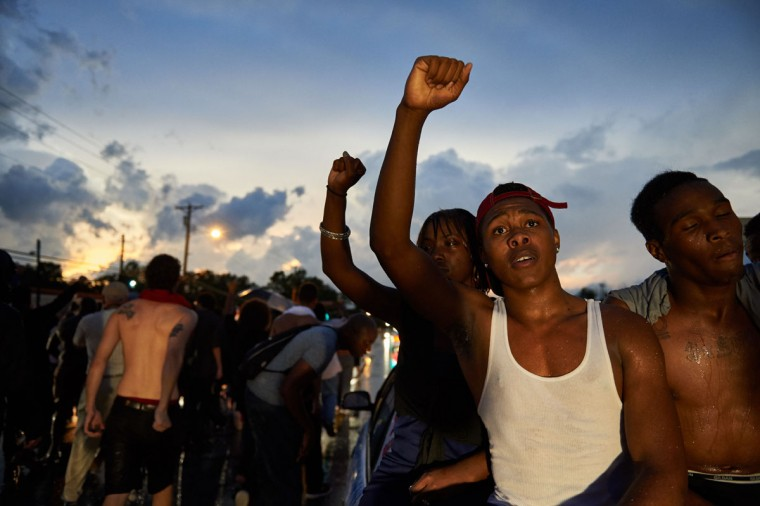 Demonstrators participate in a protest march on August 9, 2015 on West Florissant Avenue in Ferguson, Missouri, marking the one year anniversary of an unarmed black teen, Michael Brown, who was shot and killed by a white police officer, throwing America's troubled race relations into harsh relief. (AFP Photo/Michael Thomasmichael b. thomas)