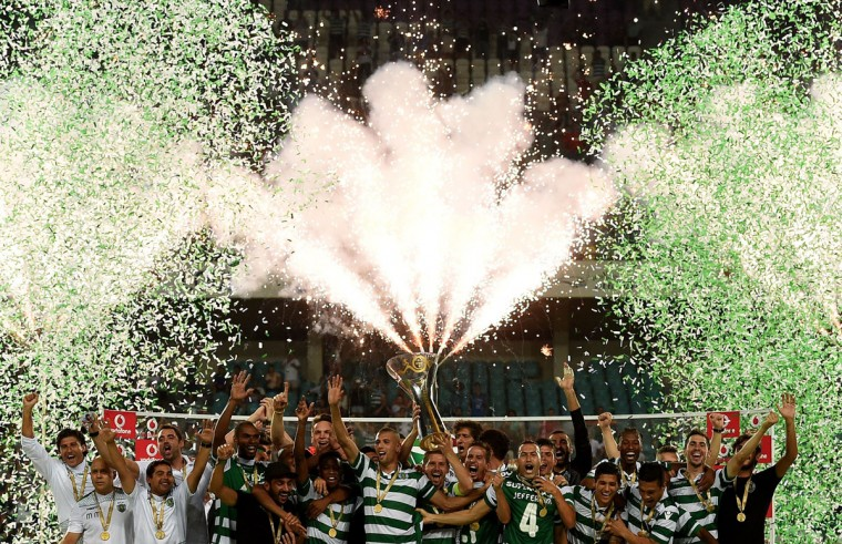 Fireworks explode as Sporting's players raise the trophy after their 1-0 victory on the Super Cup football match SL Benfica vs SC Sporting at the Algarve stadium in Faro on August 9, 2015. (AFP Photo/Francisco Leong)