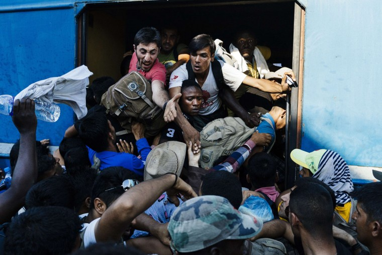 Migrants rush as they try to get on a train heading to the border with Serbia at the train station of Gevgelija, on the Macedonian-Greek border, on August 9, 2015. Non-EU Serbia's frontier with Hungary, which is in the bloc's passport-free Schengen zone, has become a major crossing point for the huge numbers of migrants entering the EU. (AFP Photo/Dimitar Dilkoff)