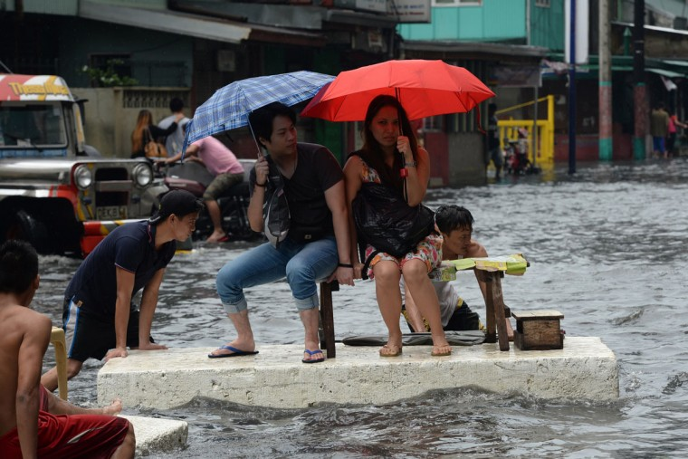 Officer workers ride on a makeshift raft made of styrofoam after a sudden heavy downpour inundated streets in the financial district of Manila on August 12, 2015, stranding thousands of commuters and office workers, with the weather bureau saying the downpour was caused by thunderstorm. Hundreds of people are killed in natural disasters each year in the Philippines, which is battered by an average of 20 typhoons and tropical storms annually. (AFP Photo/Ted Aljibe)