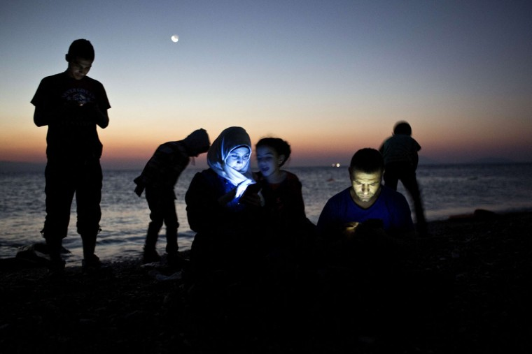 "Migrants check their mobile phones after getting out of an inflatable boat on a beach on the Greek island of Kos, after crossing a part of the Aegean Sea between Turkey and Greece, on August 12, 2015. The number of migrants and refugees arriving on Greece's shores has exploded this year, but the Mediterranean country provides virtually no reception facilities and leaves them wallowing in ""totally shameful"" conditions, a UN official said on August 7. The UN refugee agency's division for Europe said 124,000 refugees and migrants have landed in Greece since the beginning of the year. (AFP Photo/Angelos Tzortzinis)"