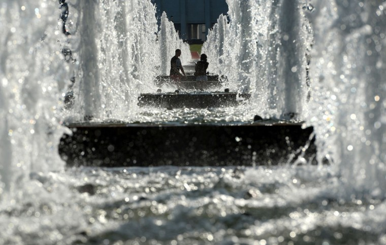 A couple walk past fountains in central Moscow on August 12, 2015. (AFP Photo/Vasily Maximov)