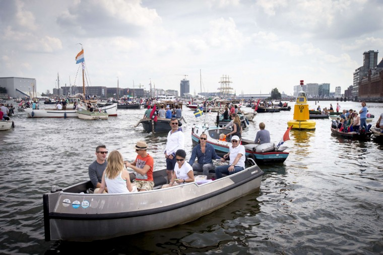 People gather on boats to see the Tall Ships accompanied by smaller boats entering Amsterdam on August 19, 2015, for the five-yearly event Sail. (JERRY LAMPEN/AFP/Getty Images)
