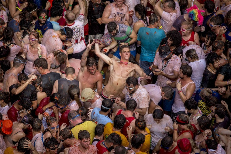 "Revelers throw tomato pulp at each other during the annual ""tomatina"" festivities in the village of Bunol, near Valencia on August 26, 2015. Some 22,000 revelers hurled 150 tons of squashed tomatoes at each other drenching the streets in red in a gigantic Spanish food fight marking the 70th annual ""Tomatina"" battle. (AFP Photo/Biel Alino)"
