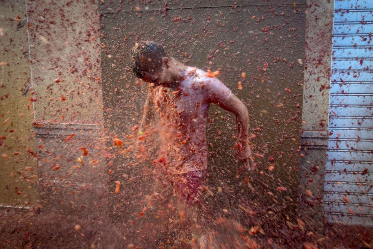 "A reveler is pelted with tomato pulp during the annual ""tomatina"" festivities in the village of Bunol, near Valencia on August 26, 2015. Some 22,000 revelers hurled 150 tons of squashed tomatoes at each other drenching the streets in red in a gigantic Spanish food fight marking the 70th annual ""Tomatina"" battle. (AFP Photo/Biel Alino)"