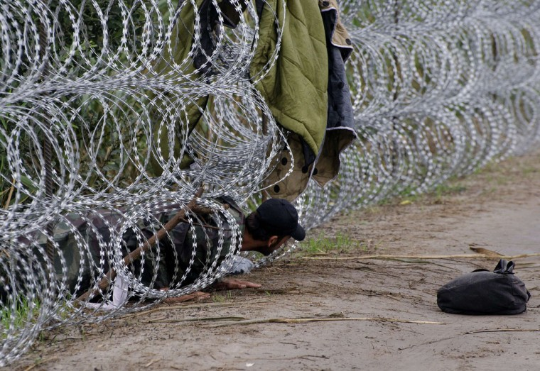 A migrant man creeps under the metal fence near the village of Roszke, at the Hungarian-Serbian border on August 26, 2015. More than 140,000 migrants have reached Hungary on routes across the Balkans so far in 2015. Recently, some 80 percent of them are from war zones like Syria, Iraq and Afghanistan. (AFP Photo/Csaba Segesvari)
