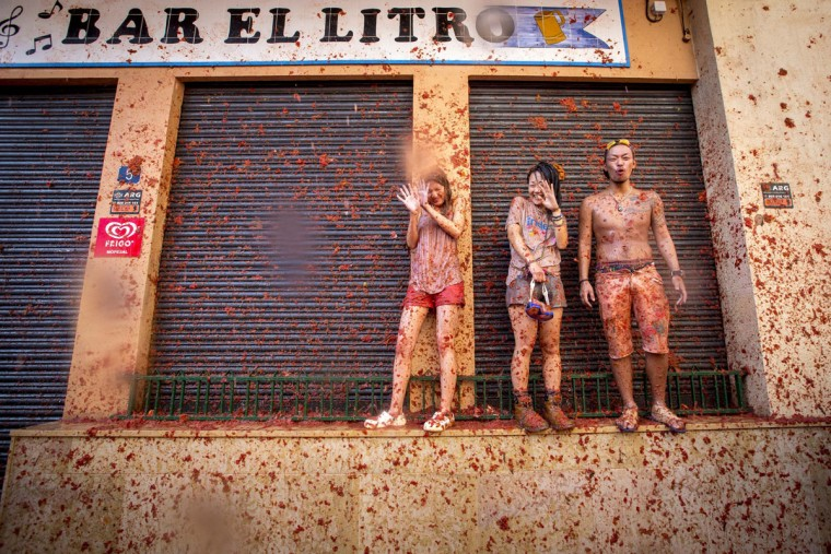 "Revelers covered in tomato pulp stand on a wall during the annual ""tomatina"" festivities in the village of Bunol, near Valencia on August 26, 2015. Some 22,000 revelers hurled 150 tons of squashed tomatoes at each other drenching the streets in red in a gigantic Spanish food fight marking the 70th annual ""Tomatina"" battle. (AFP Photo/Biel Alino)"
