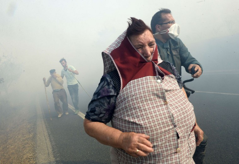 A Civil Guard helps villagers during a fire in the village of Cabreiro, some 60 km from Ourense, northwestern Spain, on August 30, 2015. (AFP Photo/Miguel Riopa)