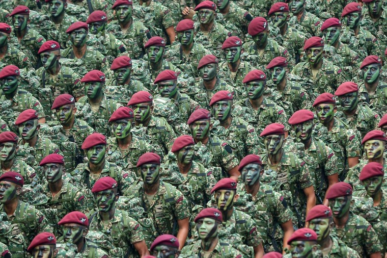 Members of Malaysia's military parade past during National Day celebrations at Independence Square in Kuala Lumpur on August 31, 2015. Malaysia's government reclaimed the streets of the capital on August 31 after massive weekend protests demanding the premier's ouster, staging its own show of force with colourful National Day celebrations attended by thousands. (AFP Photo/Mohd Rasfan)