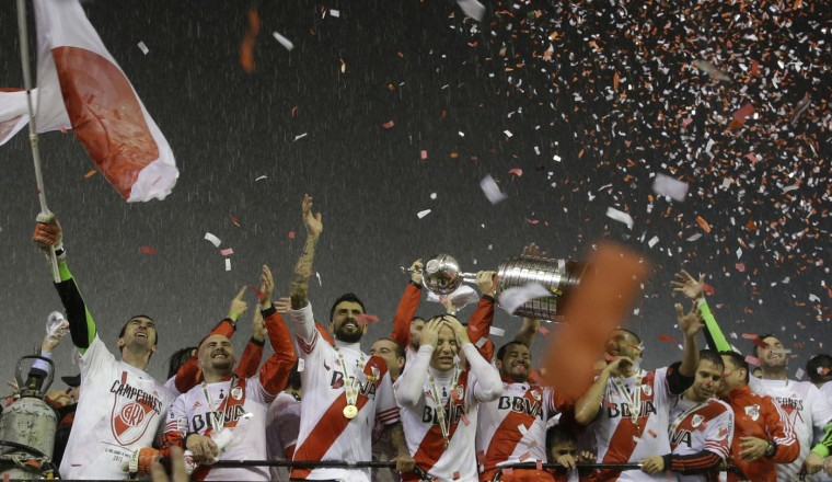 Argentina's River Plate players hold the trophy aloft while they celebrate winning the the Copa Libertadores final soccer match against Mexico's Tigres in Buenos Aires, Argentina, Thursday, Aug. 6, 2015. River defeated Tigres 3-0 and became the tournament champions. (AP Photo/Ivan Fernandez)