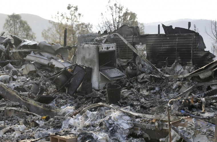 Burned remains of a property is shown near Clearlake, Calif., Wednesday, Aug. 5, 2015. Thousands of firefighters battling an unruly Northern California wildfire were aided overnight by cooler temperatures and higher humidity, but the fire is still less than a quarter contained. (AP Photo/Jeff Chiu)