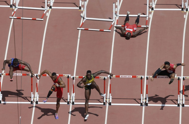 Trinidad and Tobago's Mikel Thomas, top, lies on the track after falling in a menís 110m hurdles round one heat at the World Athletics Championships at the Bird's Nest stadium in Beijing, Wednesday, Aug. 26, 2015. (AP Photo/Wong Maye-E)