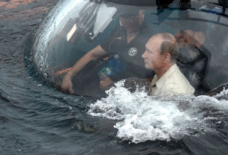 Russian President Vladimir Putin, right, sits on board a bathyscaphe as it plunges into the Black sea along the coast of Sevastopol, Crimea, Tuesday, Aug. 18, 2015. President Vladimir Putin plunged into the Black Sea to see the wreckage of a sunk ancient merchant ship which was found in the end of May. (Alexei Nikolsky/RIA-Novosti, Kremlin Pool Photo via AP)