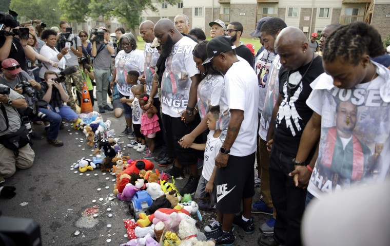 Michael Brown Sr. along with family and friends stop to pray at a memorial to Brown's son before taking part in a parade in his son's honor Saturday, Aug. 8, 2015, in Jennings, Mo. Sunday will mark one year since Michael Brown was shot and killed by Ferguson police officer Darren Wilson. (AP Photo/Jeff Roberson)