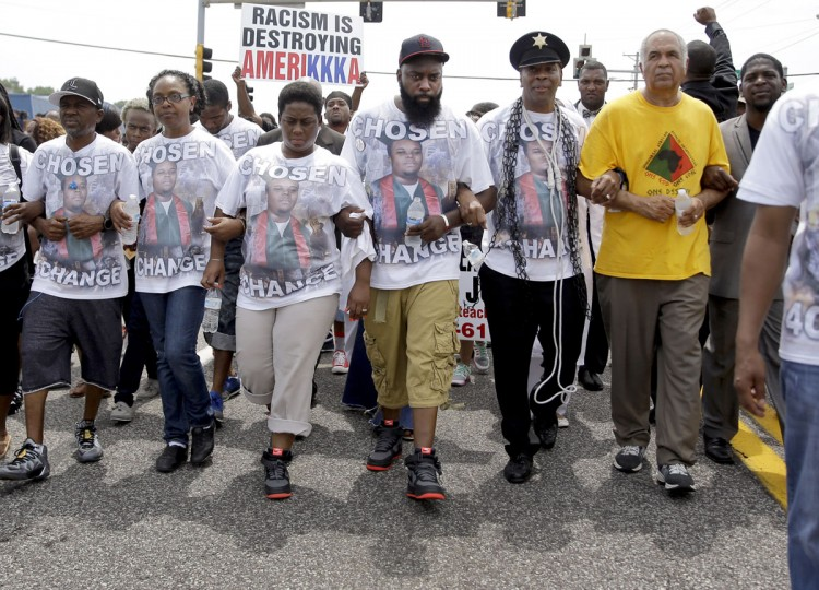 Michael Brown Sr., center, takes part in a march in remembrance of his son, Michael Brown, Sunday, Aug. 9, 2015, in Ferguson, Mo. Sunday marks one year since Michael Brown was shot and killed by Ferguson police officer Darren Wilson. (AP Photo/Jeff Roberson)