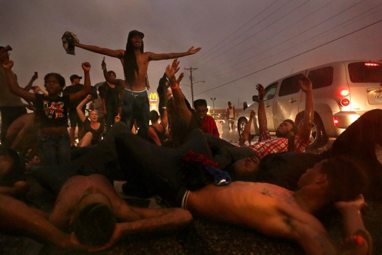 People protest on West Florissant Ave., Sunday, Aug. 9, 2015, in Ferguson, Mo., on the one-year anniversary of Michael Brown being shot and killed by Ferguson Police Officer Darren Wilson. (Cristina M. Fletes/St. Louis Post-Dispatch via AP)