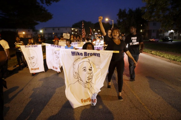 Protesters march down Canfield Drive near where Michael Brown was killed Friday, Aug. 7, 2015, in Ferguson, Mo. Sunday will mark one year since Brown was fatally by Ferguson police officer Darren Wilson. (AP Photo/Jeff Roberson)