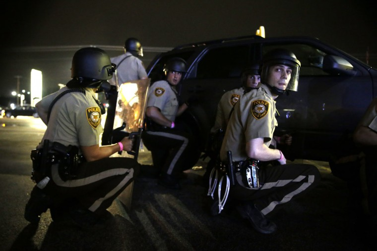 Police take cover behind a vehicle during a protest in Ferguson, Mo., Sunday, Aug. 9, 2015. The one-year anniversary of Michael Brown's death in Ferguson began with a march in his honor and ended with a protest that was interrupted by gunfire. (AP Photo/Jeff Roberson)