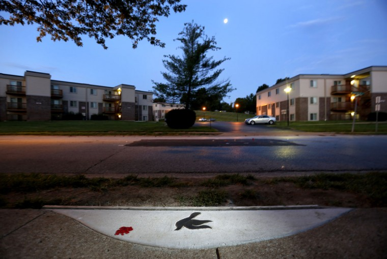"A marker in the shape of a dove is embedded in the sidewalk near the spot where Michael Brown was shot and killed by police officer Darren Wilson in Ferguson, Mo. A year ago, Ferguson was thrust into the national spotlight after the death of Brown giving way to the ""Black Lives Matter"" movement. (AP Photo/Jeff Roberson)"