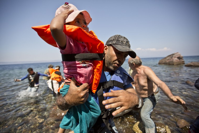 Syrian migrant holds his daughter while rushing to shore upon their arrival on a dinghy in the village of Skala Sikaminea at the southeastern Greek island of Lesbos, Greece, Thursday, Aug. 20, 2015. Greece this year has been overwhelmed by record numbers of migrants arriving on its eastern Aegean islands, with more than 160,000 landing so far. (AP Photo/Visar Kryeziu)