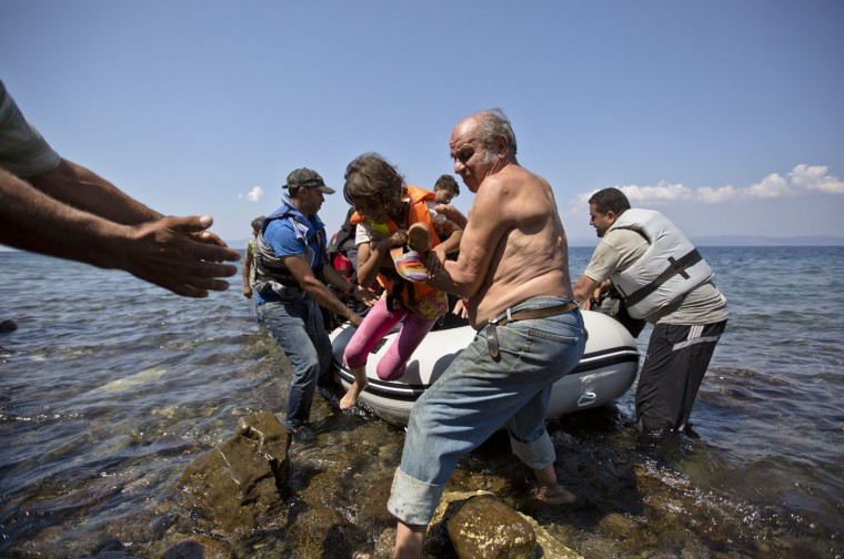 A local helps a Syrian migrant child upon their arrival on a dinghy in the village of Sikaminies, at the southeastern Greek island of Lesbos, Greece, Thursday, Aug. 20, 2015. Greece this year has been overwhelmed by record numbers of migrants arriving on its eastern Aegean islands, with more than 160,000 landing so far. (AP Photo/Visar Kryeziu)