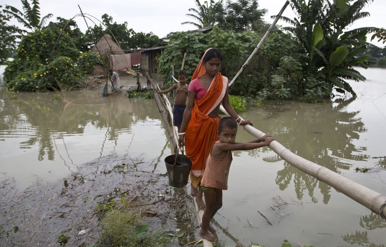 Locals affected by monsoon rains walk through a makeshift bridge in Mayong village, about 55 kilometers (34 miles) east of Gauhati, India, Sunday, Aug. 23, 2015. The flooding in India's northeastern Assam state is the worst in the past three years, affecting nearly 600,000 people in 19 of the state's 27 districts, officials said. (AP Photo/Anupam Nath)