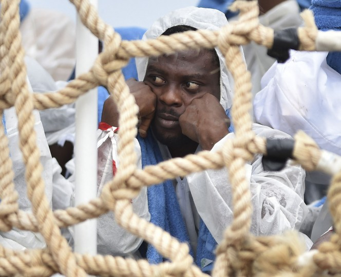 A migrant shelters from rain as he waits to disembark from Italian Coast Guard ship Oreste Corsi, at the Messina harbor in Sicily, Italy, Tuesday, Aug. 4, 2015. Italy's Coast Guard rescued 306 migrants on Tuesday, and took them safely to land in Messina as the migrants death toll for 2015 reached in August over 2000 victims, and IOM called the Channel of Sicily the deadliest route for migrants in search of a better life. (AP Photo/Carmelo Imbesi)