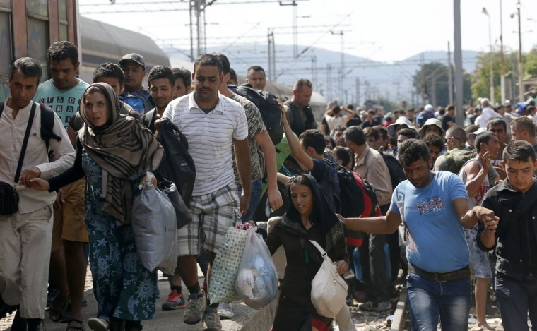 Migrants rush to board a train that would take them towards Serbia, at the railway station in the southern Macedonian town of Gevgelija, Wednesday, Aug. 19, 2015. Record numbers of migrants from countries like Syria, Iraq and Afghanistan use the so-called Balkan route that passes trough Macedonia. (AP Photo/Darko Vojinovic)