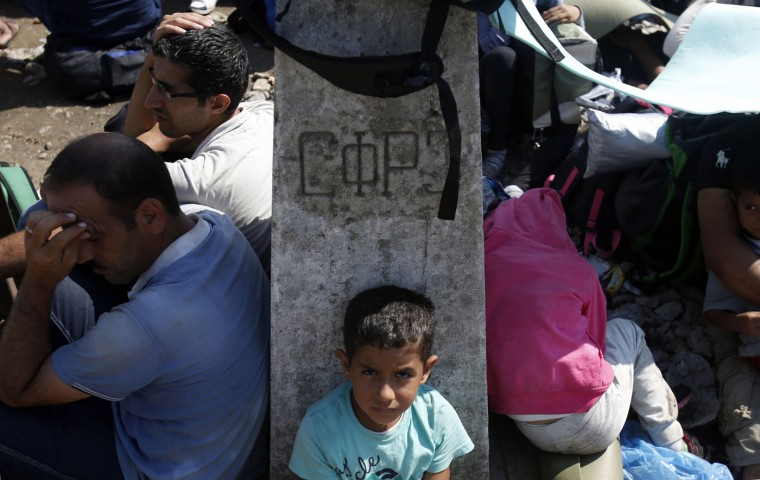 "Blocked migrants wait by border stone with sign that reads: ""Socialist Federal Republic of Yugoslavia"" at the at no-man's land between Greece and Macedonia near the southern Macedonian town of Gevgelija, Thursday, Aug. 20, 2015. Thousands of migrants were stranded Thursday on no-man's land between Macedonia and Greece, from where they planned to catch trains that would take them to the Serbian border on their way to EU-member Hungary. (AP Photo/Darko Vojinovic)"