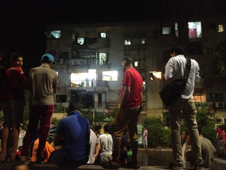 People gather near the scene where a bomb exploded early Thursday, Aug. 20, 2015, near a national security building in the Shubra neighborhood of Cairo. For blocks around the blast site in the popular residential neighborhood, glass from blown-out windows could be seen on the street. (AP Photo/Brian Rohan)