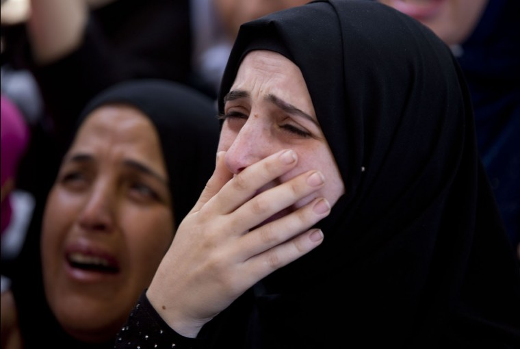 A relative of Palestinian Mohammed Amsha, 25, cries during his funeral in the village of Kafr Rai near the West Bank city of Jenin, Tuesday, Aug. 18, 2015. Israeli authorities say Amsha was shot and killed after he stabbed a guard at a West Bank checkpoint, slightly wounding him. (AP Photo/Majdi Mohammed)