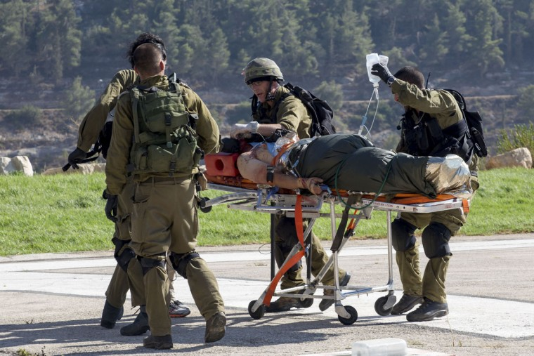 Israeli soldiers transport a wounded Israeli man to Hadassah Ein Kerem Hospital in Jerusalem after he was evacuated by helicopter, Thursday, Aug 6, 2015. A Palestinian motorist rammed his car into pedestrians near the West Bank Jewish settlement of Shilo, wounding three Israelis before he was shot by Israeli troops, the military said. (AP Photo/Emeil Salman)