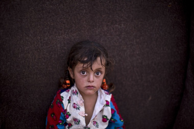 Syrian refugee girl Zahra Mahmoud, 4, sits in front of her family's makeshift tent at an informal tented settlement near the Syrian border on the outskirts of Mafraq, Jordan, Wednesday, Aug. 19, 2015. (AP Photo/Muhammed Muheisen)