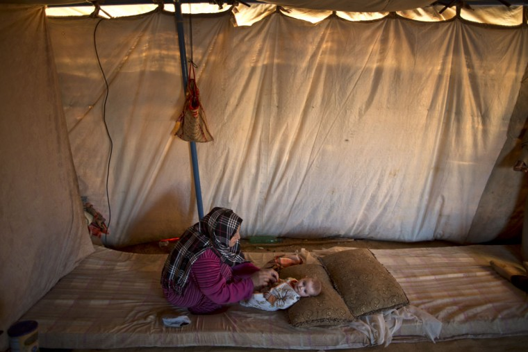 In this Tuesday, July 21, 2015 photo, Syrian refugee Naela Mohammed, 31, changes the clothes of her daughter Asmahan, 4 months, at their tent in an informal tented settlement near the Syrian border on the outskirts of Mafraq, Jordan. Naela worries about being able to nurse her child while she herself doesnít have enough to eat. ìItís a sure thing my 4-month daughter will be paying the price,î Mohammed says. ìSheís so tiny and weak.î (AP Photo/Muhammed Muheisen)
