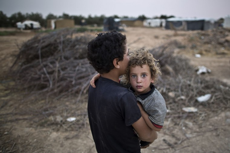 A Syrian refugee boy carries his younger brother back to their tent at an informal tented settlement near the Syrian border on the outskirts of Mafraq, Jordan, Tuesday, Aug. 4, 2015. (AP Photo/Muhammed Muheisen)