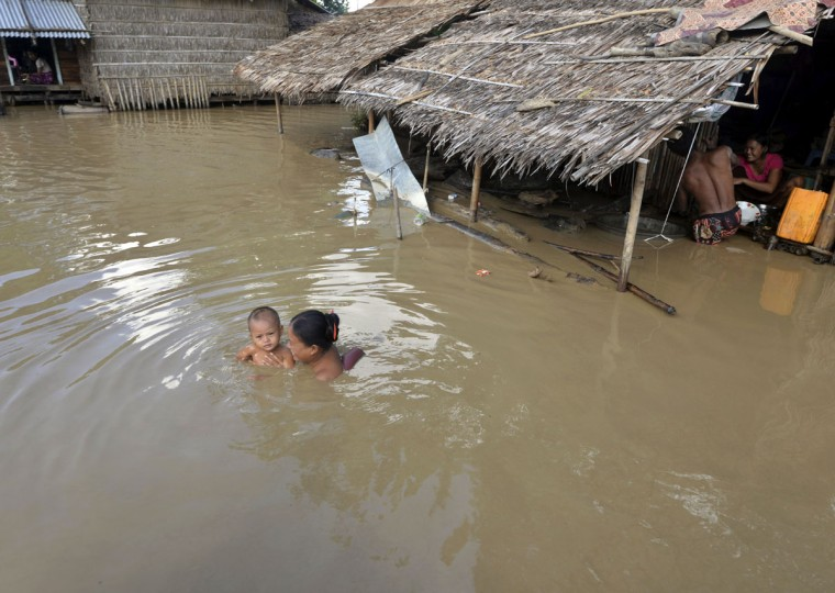 In this Sunday, Aug. 9, 2015 photo, a woman swims with her child near their half-submerged residence in Zalun township, Ayeyarwaddy delta, Myanmar. The number of people affected by flooding across Myanmar was approaching 1 million on Sunday, with waters in the low-lying southwestern delta inundating homes and forcing villagers into temporary shelters, the government said. (AP Photo/Khin Maung Win)