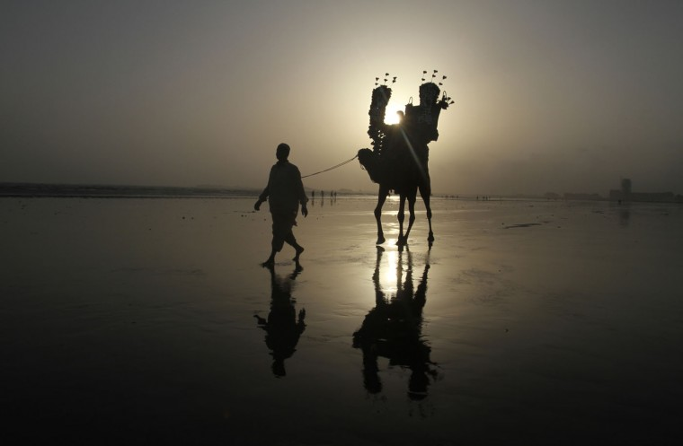 A Pakistani family enjoy a camel ride at the Karachi beach, in Pakistan, Tuesday, Aug. 4, 2015 in Pakistan. (AP Photo/Fareed Khan)