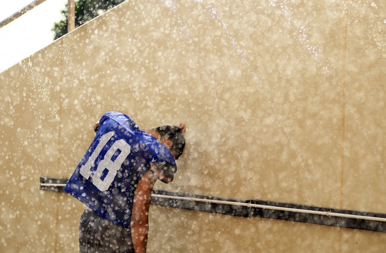 A West Scranton High School football player briefly cools off at a water station during a break in practice on a hot and humid, Tuesday, Aug. 18, 2015, at the West Scranton Intermediate School in Scranton, Pa. (Butch Comegys/The Times & Tribune via AP)