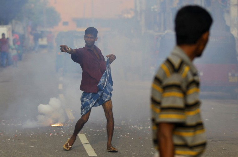 A supporter of Sri Lanka's ruling United National Party dances on a road amid exploding fire crackers as he celebrates the party's election performance in Colombo, Sri Lanka, Tuesday, Aug. 18, 2015. Sri Lanka's prime minister Ranil Wickremesinghe has defeated the country's former strongman Mahinda Rajapaksa in parliamentary elections, blocking his attempted political comeback eight months after he lost the presidency. (AP Photo/Eranga Jayawardena)