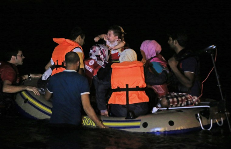 Migrants, including one carrying a crying infant, board a dinghy to begin their journey from near the coastal town of Bodrum, Turkey, to cross to the nearby Greek island of Kos, early Thursday, Aug. 20, 2015. With the shores of Kos - a gateway to Europe - just a few kilometers (miles) away, hundreds of migrants are piling into tiny inflatable dinghies each night and attempting to make the crossing powered by tiny outboard motors and plastic paddles. (AP Photo/Lefteris Pitarakis)
