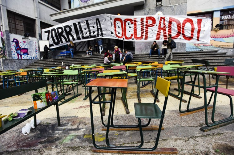 Student's desks sit in the street outside Zorilla High School, placed there by striking high school teachers in Montevideo, Uruguay, Thursday, Aug. 20, 2015. Teachers unions are on strike before the nation's budget is presented on Aug. 31, which will lay out Uruguay's public spending plan for the next five years. Teachers are demanding raises and more funding for education. (AP Photo/Matilde Campodonico)