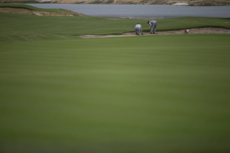In this July 22, 2015 photo, personnel work at the Olympic Golf Course in Rio de Janeiro, Brazil. Once the Olympics are over, luxury housing units at the golf course will be sold. The project involve public and private money, with much of the income going to the private developers. (AP Photo/Silvia Izquierdo)