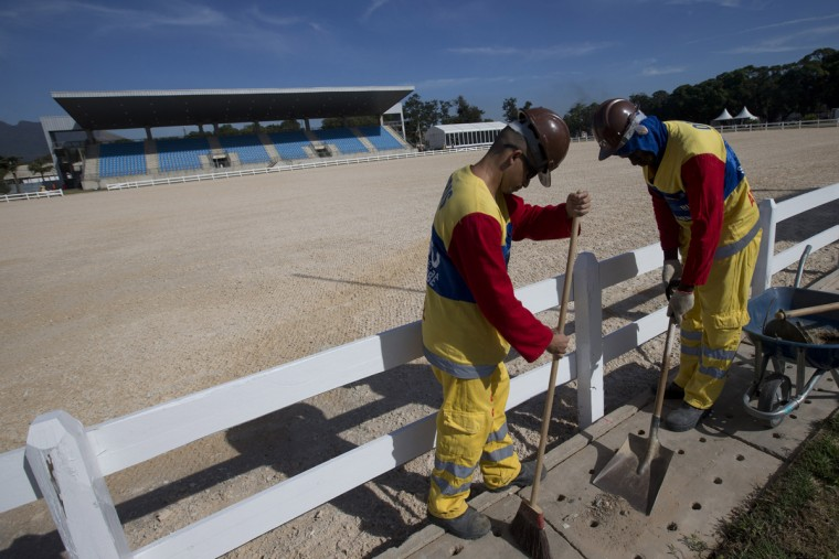In this July 20, 2015 photo, Personnel work at the Olympic Equestrian Center in Rio de Janeiro, Brazil. Construction for the Olympics got off to a slow start. And so did ticket sales.(AP Photo/Silvia Izquierdo)