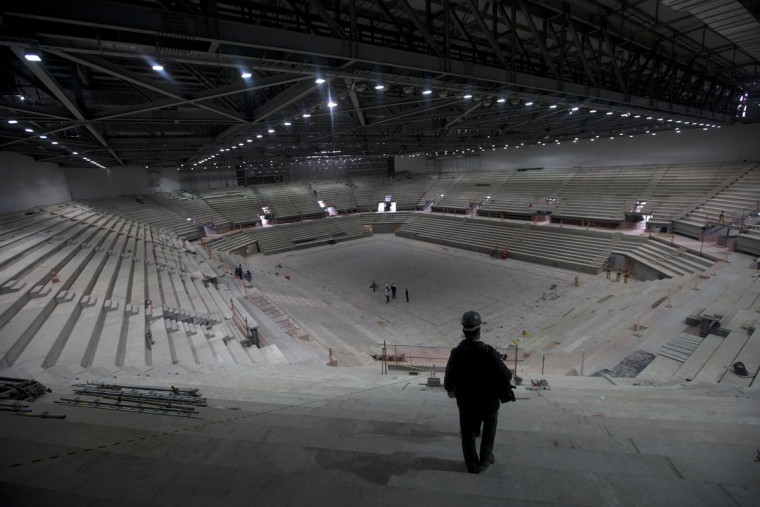 In this July 22, 2015 photo, a journalist walks in the Future Arena which will host the handball competition during the Olympic Games in Rio de Janeiro, Brazil. With a year to go before the Rio Olympics open, organizers struggle to have all the buildings completed, clean the water in several badly polluted venues for rowing and sailing, and get an efficient transportation network in place to tame one of the world's most congested cities. (AP Photo/Silvia Izquierdo)
