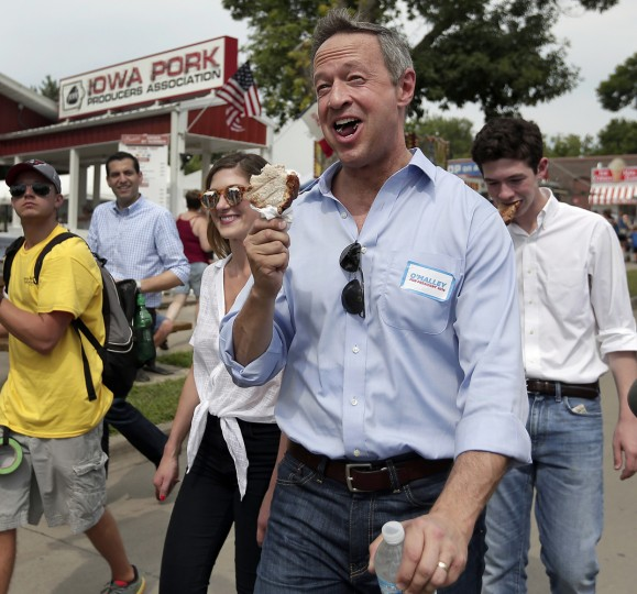 """Democratic presidential candidate, former Maryland Gov. Martin O'Malley, eats a """"pork chop on a stick"""" at the Iowa State Fair Thursday, Aug. 13, 2015, in Des Moines. (AP Photo/Charlie Riedel)"""