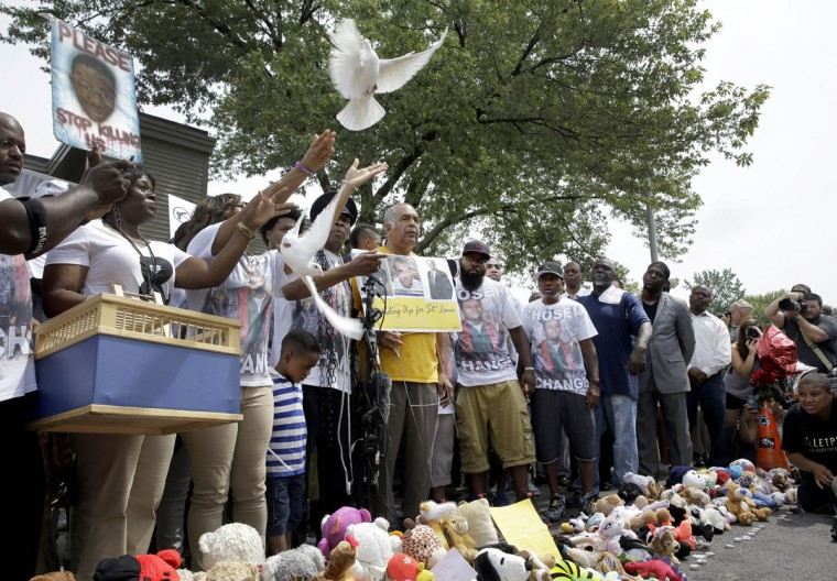 Doves are released at the moment of the one year anniversary of the death of Michael Brown during a remembrance for the 18-year-old Sunday, Aug. 9, 2015, in Ferguson, Mo. Sunday marks one year since Brown was shot and killed by Ferguson police officer Darren Wilson. (AP Photo/Jeff Roberson)