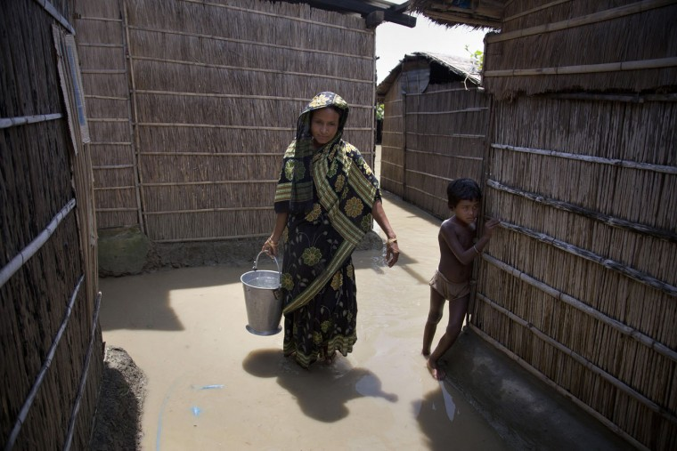 A woman carries drinking water in a bucket as she walks through flood waters at Pabhokati village, about 70 kilometres (43 miles) east of Gauhati, India, Saturday, Aug. 22, 2015. Monsoon flooding have killed several people and forced around 200,000 to leave their water-logged homes and take shelter in state-run camps this past week in India's northeastern Assam state, officials said Saturday. (AP Photo/Anupam Nath)