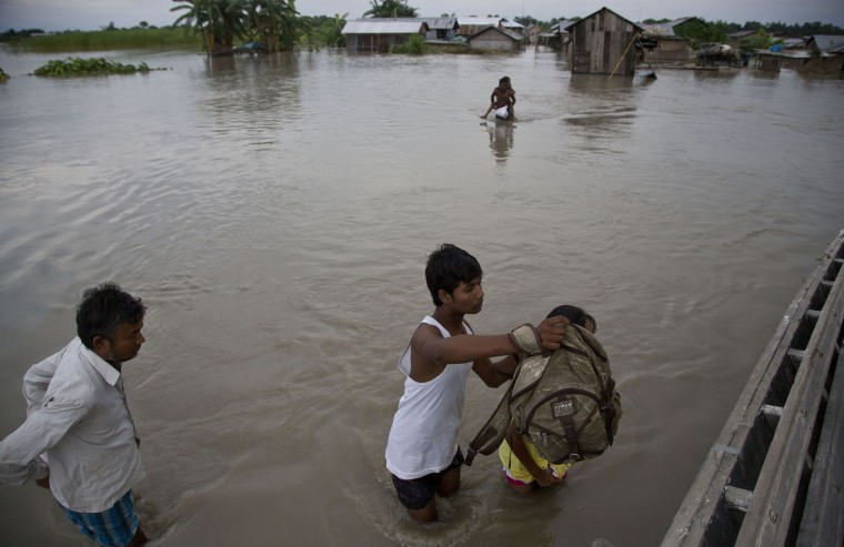 Indian villagers walk through a flood affected area in Ximolutola village, about 85 kilometers (53 miles) east of Gauhati, India , Saturday, Aug. 22, 2015. State authorities say that monsoon flooding has nearly 200,000 people to leave their homes and take shelter in state-run tents this week. The area is prone to flooding during the June-to-September monsoon season. (AP Photo/Anupam Nath)